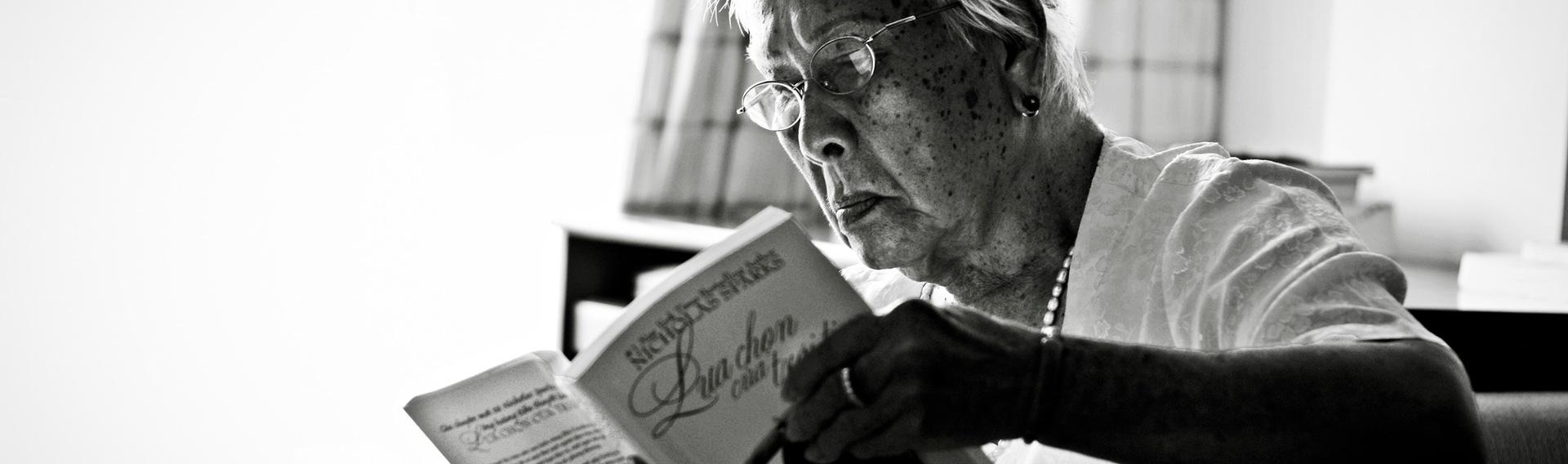 Ældre dame, der læser i et rum oplyst med Dynamisk Belysning